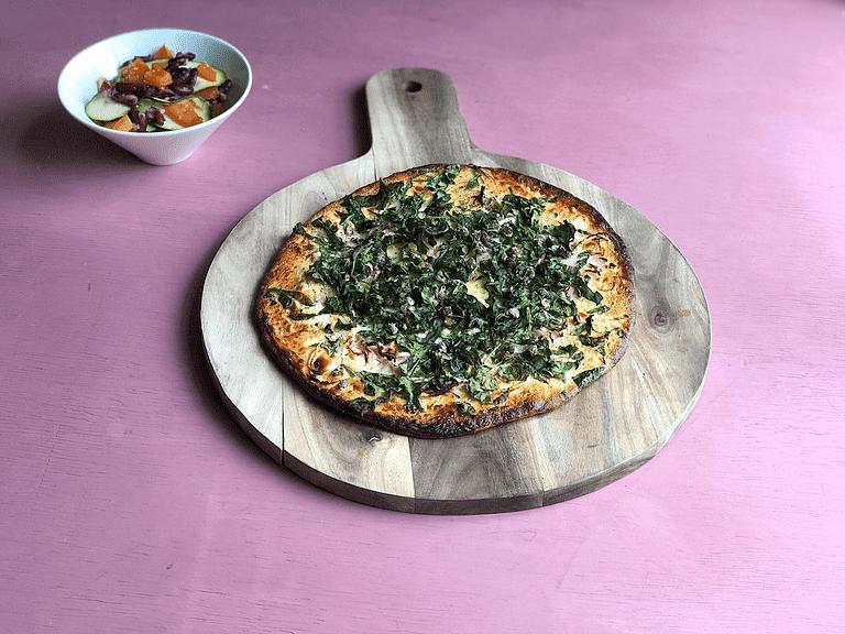 Hvid løgpizza med creme fraiche, spinat og lun bønnesalat