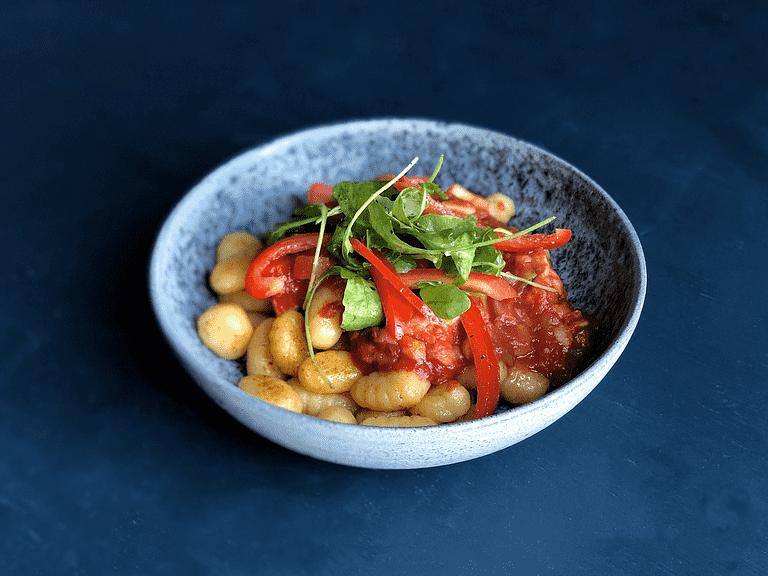 Stegt gnochetti med svinekød i tomatsauce, grønt og rucola